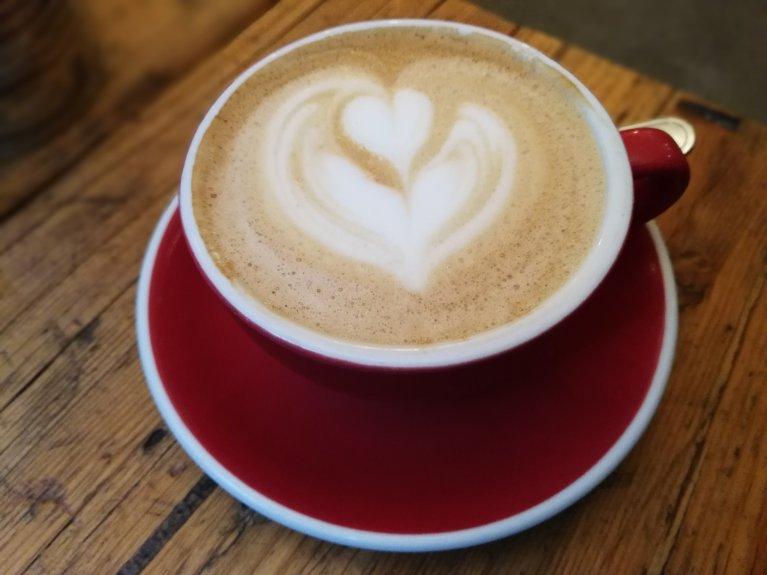 Cappuccino in een rode koffiekop met een hartje in het schuim